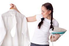 Mulher nova com camisa e ferro. Foto de Stock