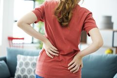 Mulher nova com dor traseira foto de stock royalty free
