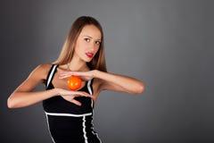Mulher nova com fruta alaranjada Foto de Stock Royalty Free