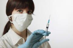 mulher nova com máscara e a seringa médicas Fotos de Stock