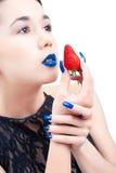 Mulher nova com morango e os pregos azuis Imagens de Stock Royalty Free
