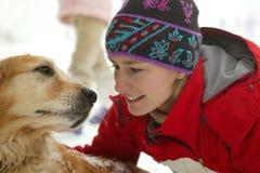 Mulher nova com o cão na neve Fotos de Stock Royalty Free