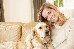 Mulher nova com o cão que senta-se no sofá Fotografia de Stock