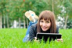 Mulher nova com o caderno no parque foto de stock