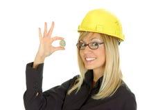 Mulher nova com o capacete de segurança que prende um dólar Imagem de Stock