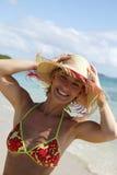 Mulher nova com o chapéu de palha na praia Imagens de Stock