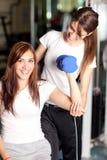 Mulher nova com o instrutor na ginástica foto de stock