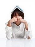 Mulher nova com o livro em sua cabeça imagem de stock royalty free