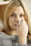 Mulher nova com o nariz de sopro frio Fotos de Stock