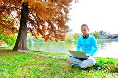 Mulher nova com o portátil no parque Fotos de Stock Royalty Free