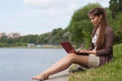 Mulher nova com o portátil no parque. Imagens de Stock