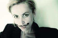 Mulher nova com o revestimento desgastando pintado do bigode Fotos de Stock