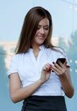 Mulher nova com o telefone nas mãos Foto de Stock Royalty Free