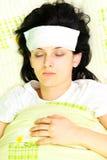 A mulher nova com olhos fechou ser doente na cama Foto de Stock Royalty Free
