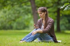 Mulher nova com os fones de ouvido no parque. Fotos de Stock Royalty Free