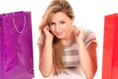 Mulher nova com os sacos de compra que encontram-se no assoalho Imagens de Stock Royalty Free