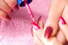 A mulher nova com pregos longos faz o manicure Foto de Stock Royalty Free