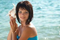 Mulher nova com seashell fotografia de stock