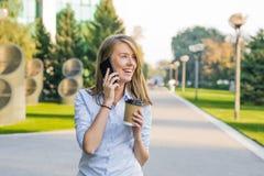Mulher nova com smartphone que anda na rua, na baixa No fundo é a rua borrada, olhando na parte dianteira Foto de Stock