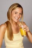 Mulher nova com sumo de laranja foto de stock