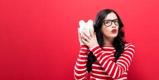 Mulher nova com um banco piggy Foto de Stock