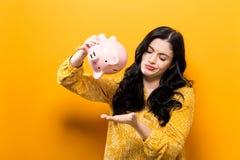 Mulher nova com um banco piggy Fotografia de Stock
