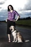 Mulher nova com um cão na estrada Foto de Stock Royalty Free