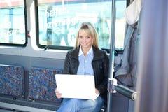 Mulher nova com um portátil dentro de um barramento Fotografia de Stock Royalty Free