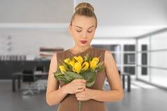 Mulher nova com um ramalhete das flores Fotografia de Stock