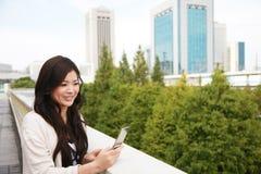 Mulher nova com um telefone móvel Imagens de Stock