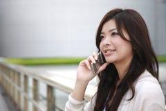 Mulher nova com um telefone móvel Fotografia de Stock Royalty Free