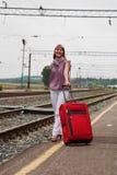 Mulher nova com uma mala de viagem vermelha Fotos de Stock Royalty Free
