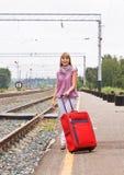 Mulher nova com uma mala de viagem vermelha Fotografia de Stock