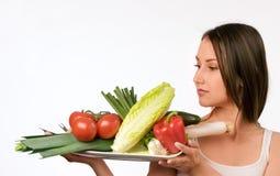 Mulher nova com uma placa de legumes frescos fotografia de stock