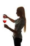 A mulher nova completa um vidro do vinho vermelho Fotos de Stock Royalty Free