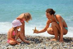 A mulher nova dá starfish a duas meninas na praia Imagens de Stock