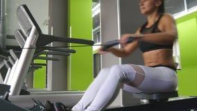 A mulher nova da aptidão faz o exercício na máquina de enfileiramento no gym Treinamento do atleta fêmea no exercitador no health filme