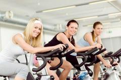 Mulher nova da aptidão no giro da bicicleta da ginástica