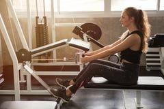 mulher nova da aptidão no sportswear que exercita os músculos de construção com cruzamento do cabo da máquina no ligth da manhã d fotografia de stock
