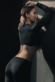 Mulher nova da aptidão no sportswear que levanta e que inclina-se no preto fotografia de stock royalty free