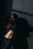 Mulher nova da aptidão no sportswear que levanta e que inclina-se no preto fotografia de stock
