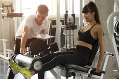 mulher nova da aptidão nos músculos dos pés dos exercícios do sportswear com a máquina do impulso com o instrutor pessoal no gym  fotos de stock