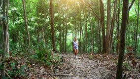 Mulher nova da aptidão que corre na floresta da selva sobre video estoque