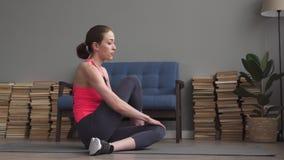 Mulher nova da aptidão que faz esticando o exercício na esteira em casa vídeos de arquivo