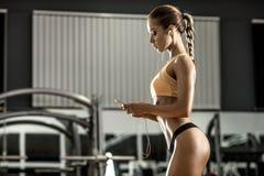 A mulher nova da aptidão cansado no gym e escuta música com auriculares Fotos de Stock