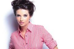 Mulher nova da beleza na camisa vermelha e no penteado agradável fotografia de stock
