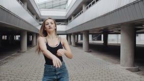 A mulher nova da dança está executando a dança moderna da moda ou do hip-hop, estilo livre em urbano industrial filme
