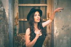Mulher nova da forma com suporte do chapéu na casa abandonada velha dianteira Imagem de Stock Royalty Free