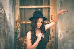 Mulher nova da forma com suporte do chapéu na casa abandonada velha dianteira Fotografia de Stock Royalty Free
