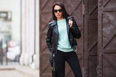 Mulher nova da forma no casaco de cabedal preto que anda na rua da cidade Fotos de Stock Royalty Free